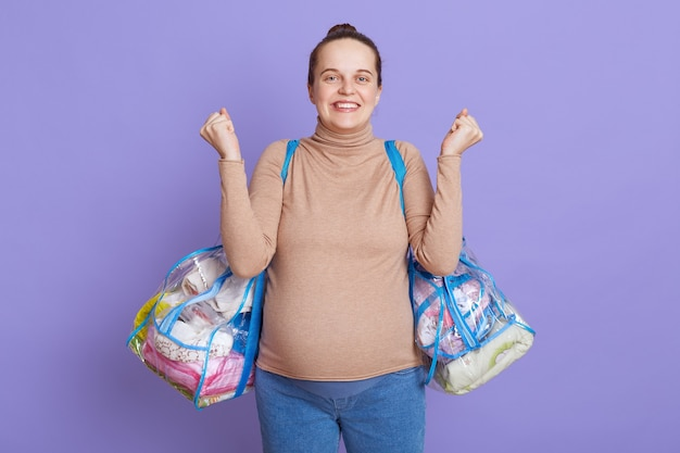Zwangere europese vrouw met haarbroodje die naar kraamkliniek vertrekt