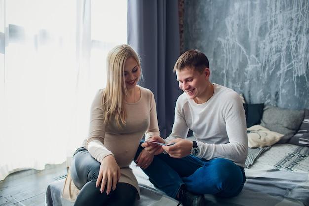 Zwangere familie met geld en kleren van de baby zitten op een sofa van het huis. gezinsbudget.