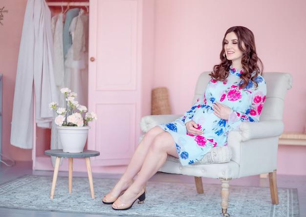 Zwangere gelukkig vrouw zit in een fauteuil