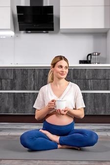 Zwangere gelukkige fitnesspersoon geniet van een kopje water of thee terwijl ze op de vloer zit na yogabeoefening thuis at