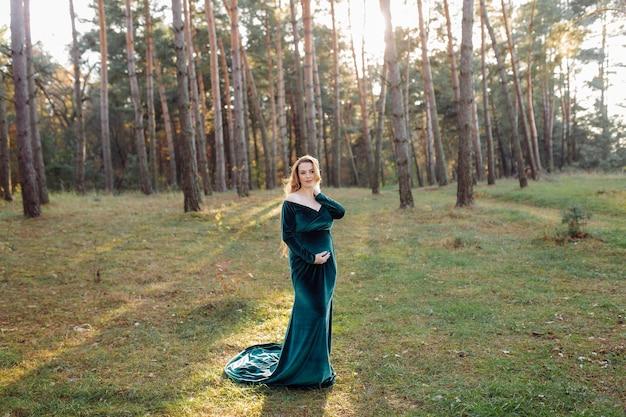 Zwangere gelukkige jonge vrouw buiten wandelen in het bos