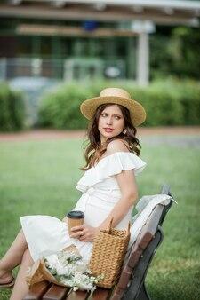 Zwangere jonge mooie vrouw drinkt cappuccino in het park