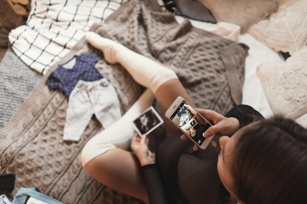 Zwangere jonge vrouw die beelden van ultrasone klankfoto's met smartphone neemt terwijl het ontspannen op een bed