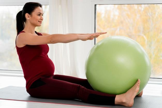 Zwangere jonge vrouw die met geschiktheidsbal uitoefent