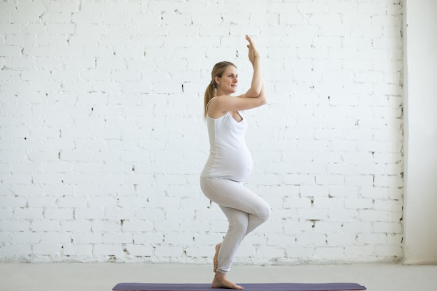 Zwangere jonge vrouw die prenatale yoga doet. eagle pose