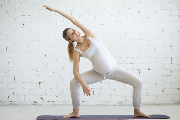 Zwangere jonge vrouw die prenatale yoga doet. godin vormt met sidebend
