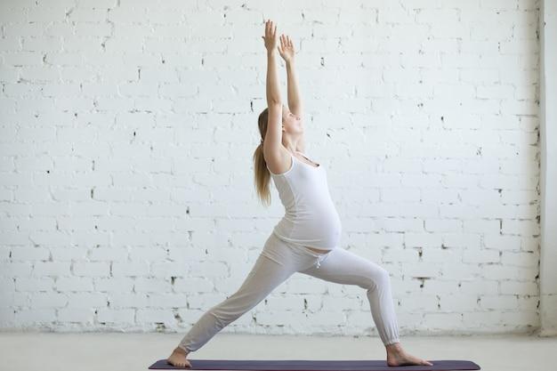 Zwangere jonge vrouw die prenatale yoga doet. warrior one poseren