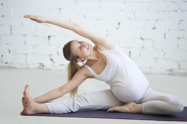 Zwangere jonge vrouw die prenatale yoga doet. zijbuiging in januar sirsasana vormen