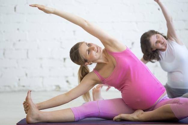 Zwangere jonge vrouwen die prenatale yoga doen. buigen in januar sirsasana vormen