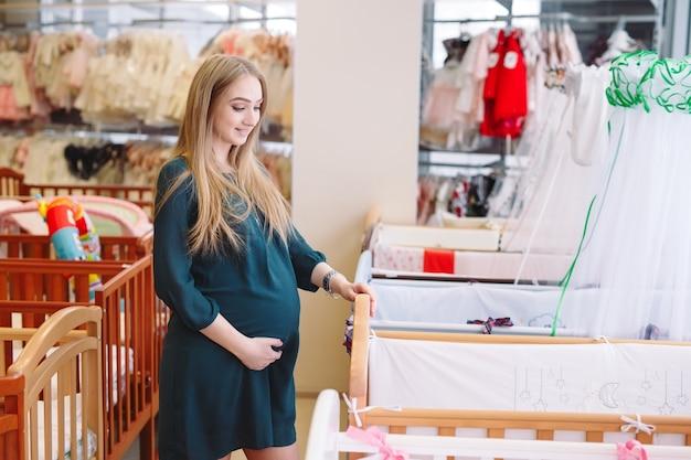 Zwangere meisje kiest een babybedje in de winkel.