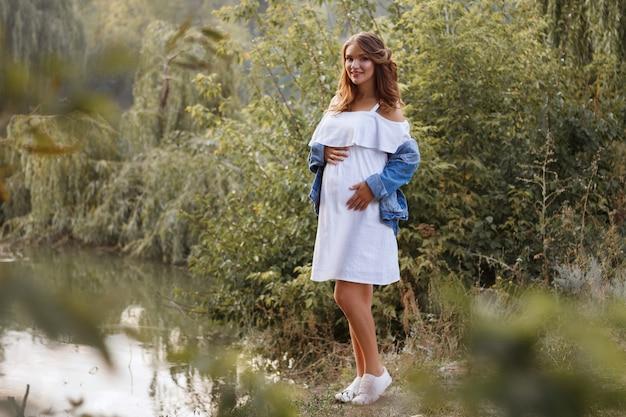 Zwangere meisje staat op het meer in de zomer