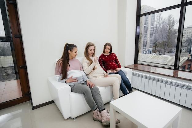 Zwangere meisjes zitten op de bank en hebben plezier met elkaar te kletsen. zwangerschap en zorgen voor de toekomst van het kind