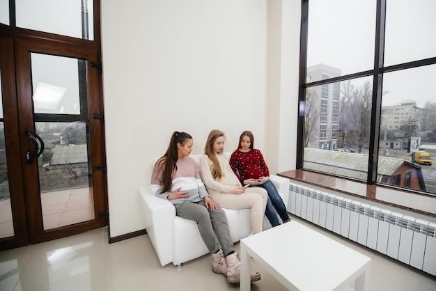 Zwangere meisjes zitten op de bank en hebben plezier met elkaar te kletsen