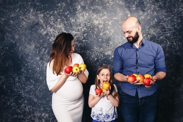 Zwangere moeder, bebaarde vader en dochtertje houden appels in hun handen en willen ze opeten. veganistisch concept