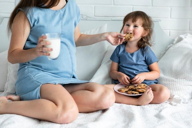 Zwangere moeder en dochter die chocoladekoekjes eten