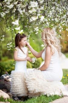 Zwangere moeder en haar dochtertje hebben buiten plezier. familie-look.