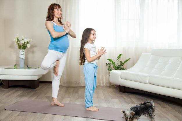 Zwangere moeder en haar meid meisje staan in yoga boom staan thuis