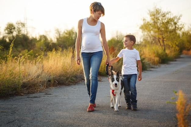 Zwangere moeder en zoon wandelen met een puppy