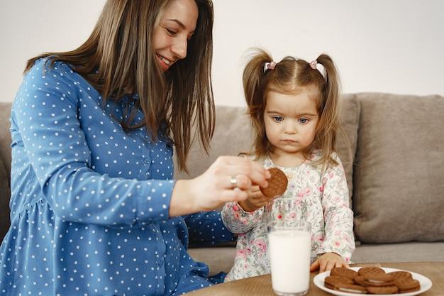 Zwangere moeder in een jurk. meisje drinkt melk. moeder en dochter genieten van koekjes.