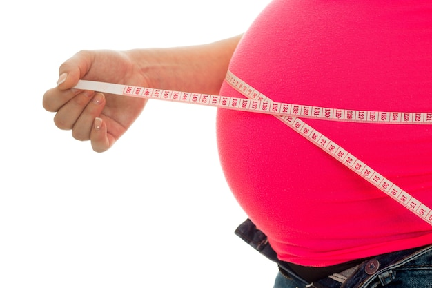 Zwangere moeder meet haar buik geïsoleerd op een witte achtergrond in studio