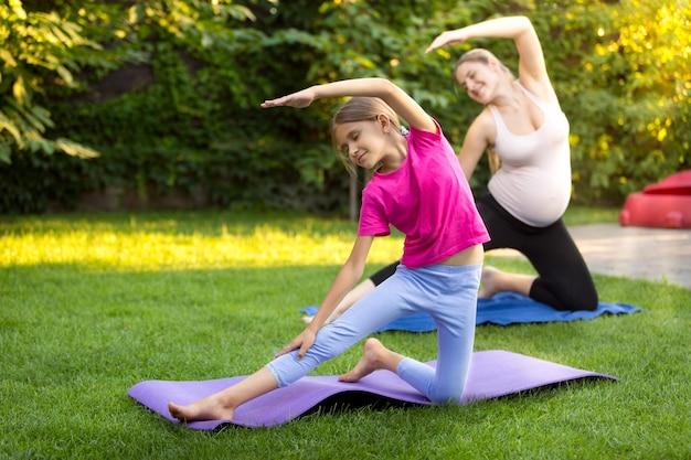 Zwangere moeder met dochter die yoga beoefent op gras in het park