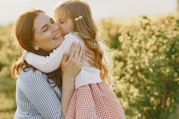 Zwangere moeder met haar dochter in een veld