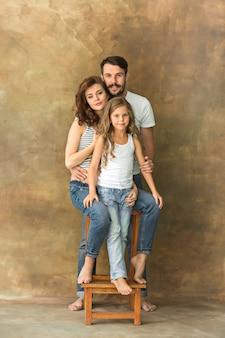 Zwangere moeder met tienerdochter en echtgenoot. het portret van de familiestudio over bruine achtergrond