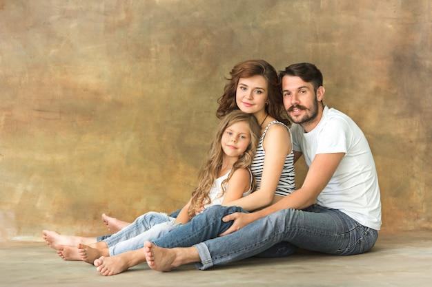 Zwangere moeder met tienerdochter en echtgenoot. het portret van de familiestudio over bruine muur