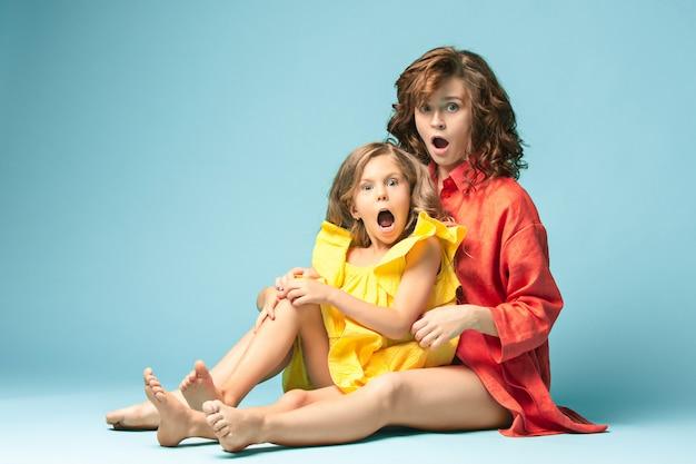 Zwangere moeder met tienerdochter. het portret van de familiestudio over blauwe achtergrond
