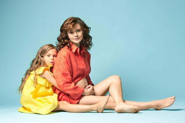 Zwangere moeder met tienerdochter. het portret van de familiestudio over blauwe muur