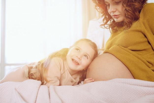 Zwangere moeder speelt met haar dochter. concept van familie, vreugde en zwangerschap