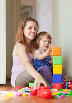 Zwangere moeder speelt met kind