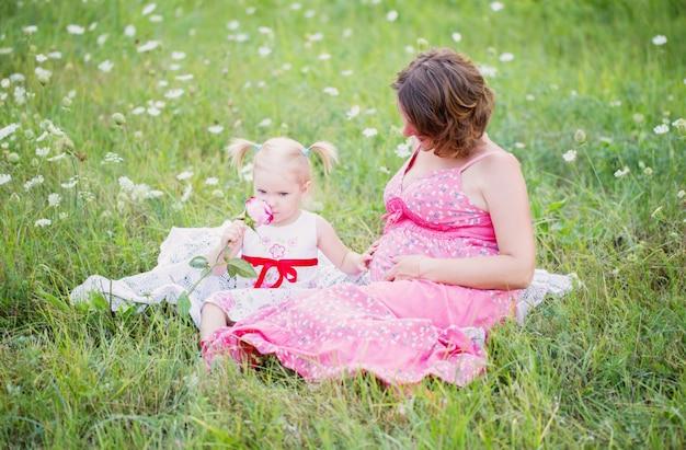Zwangere moeder spelen met haar dochter buiten