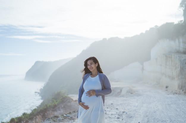 Zwangere moeder staat naast een klif
