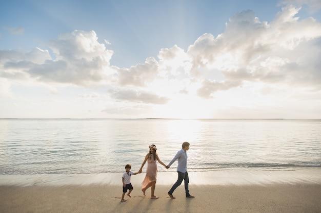 Zwangere moeder, vader en zoon wandelen op het strand