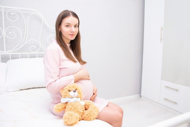 Zwangere mooi meisje zit op het bed en haar handen zijn op haar buik. concept zwangerschap, moederschap, voorbereiding en verwachting.