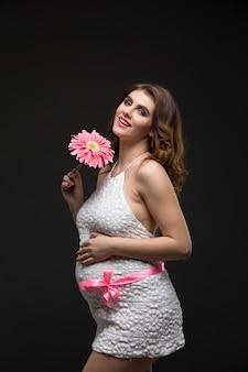 Zwangere mooie donkerbruine vrouw in witte kleding met perfect make-up en kapsel, die roze bloem houden