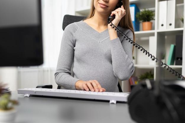 Zwangere onderneemster aan de telefoon bij haar bureau