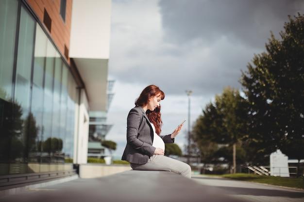 Zwangere onderneemster die digitale tablet met behulp van