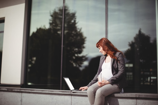 Zwangere onderneemster die laptop met behulp van