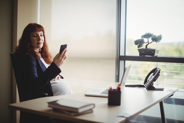 Zwangere onderneemster die mobiele telefoon met behulp van