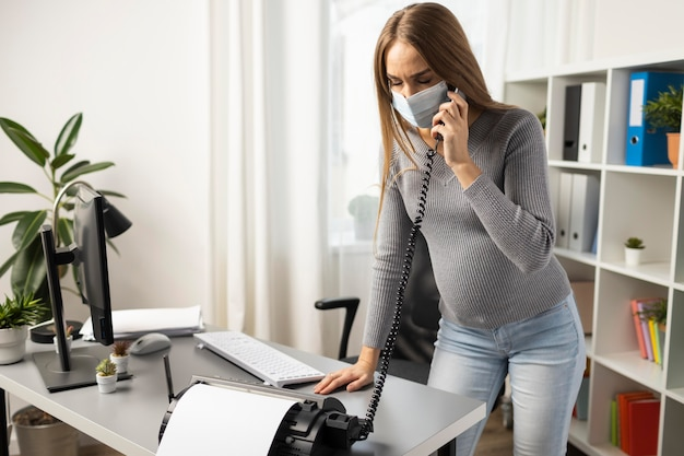 Zwangere onderneemster met medisch masker die oproepen op kantoor beantwoorden