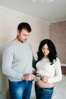 Zwangere paar bedrijf in de handen echografie van de baby