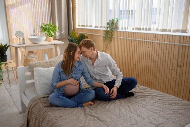 Zwangere paar knuffelen zittend op het bed