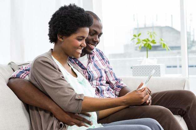 Zwangere paarzitting op bank en thuis het gebruiken van digitale tablet
