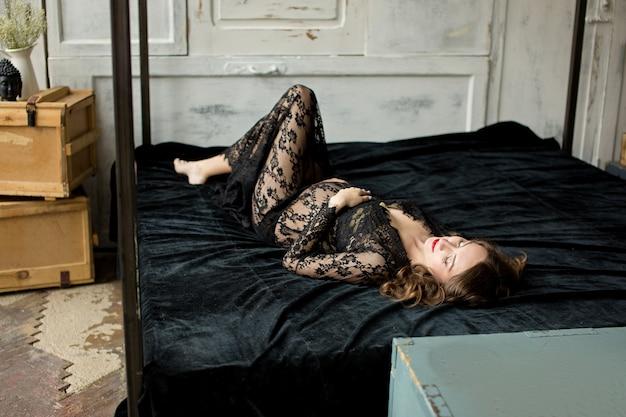 Zwangere slaperige vrouw in kanten jurk