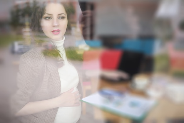 Zwangere vrouw aan het werk tijdens de lunch op de computer in café