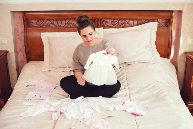 Zwangere vrouw bereidt kledingstukken voor op de pasgeboren baby. vrouw kijkt naar de kleine jurk voor dochter. moeder bereidt zich voor op de bevalling tijdens de zwangerschap.