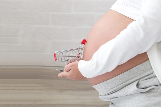 Zwangere vrouw bereidt zich voor om babyproducten te kopen vóór de geboorte, houdt winkelwagentje voor de buik, winkelen checklist tijdens zwangerschap en prenatale
