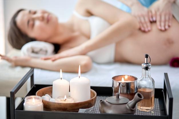Zwangere vrouw bij het fysiotherapeutkabinet dat massage krijgt, in kuuroordsalon. licht lichte kamer met kaarsen, focus op kaarsen